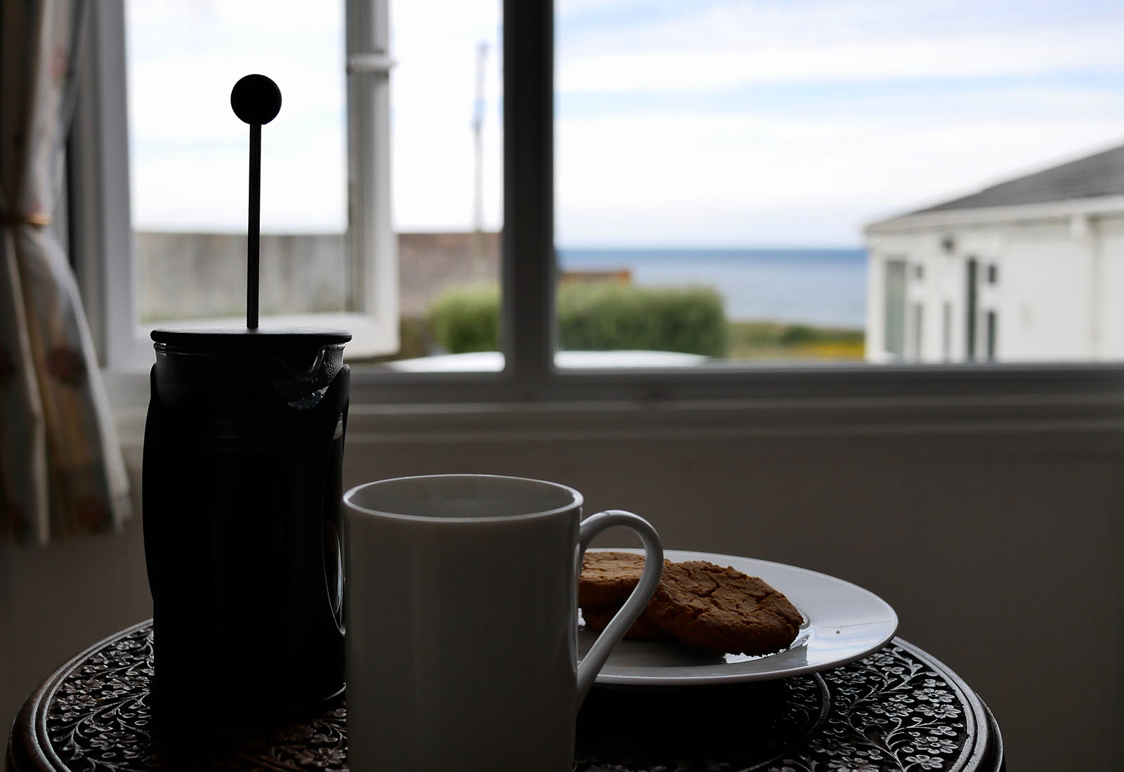 Coffee and seaview from inside a cottage.