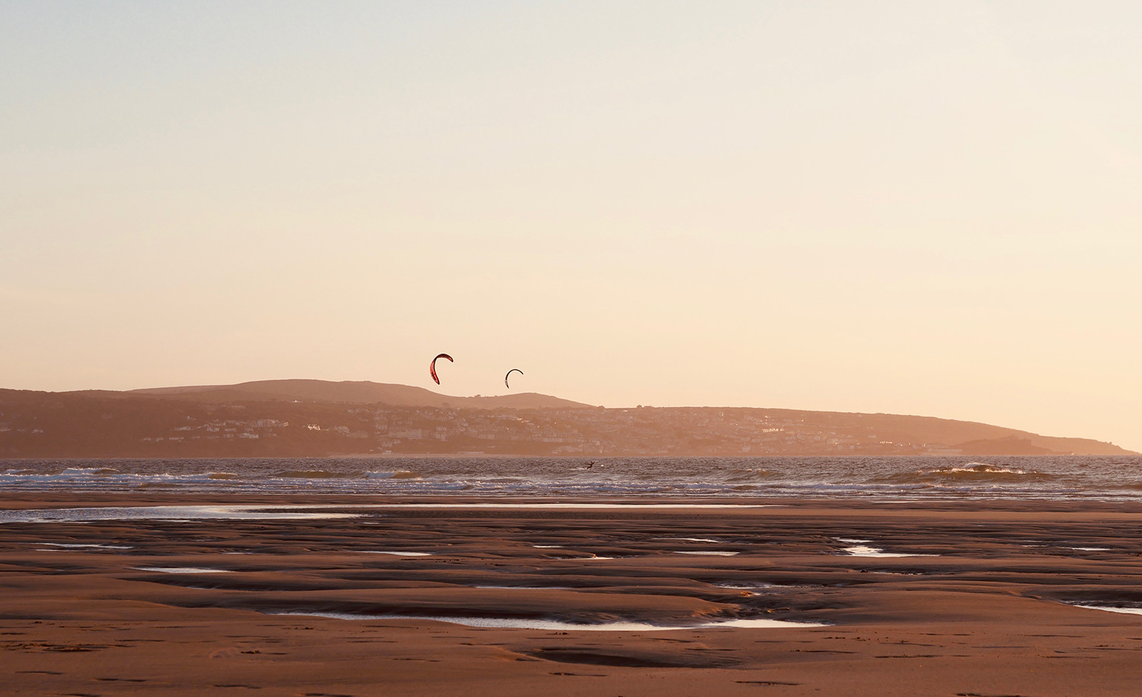 Sunset kitesurf session at Gwithian beach, Cornwall.
