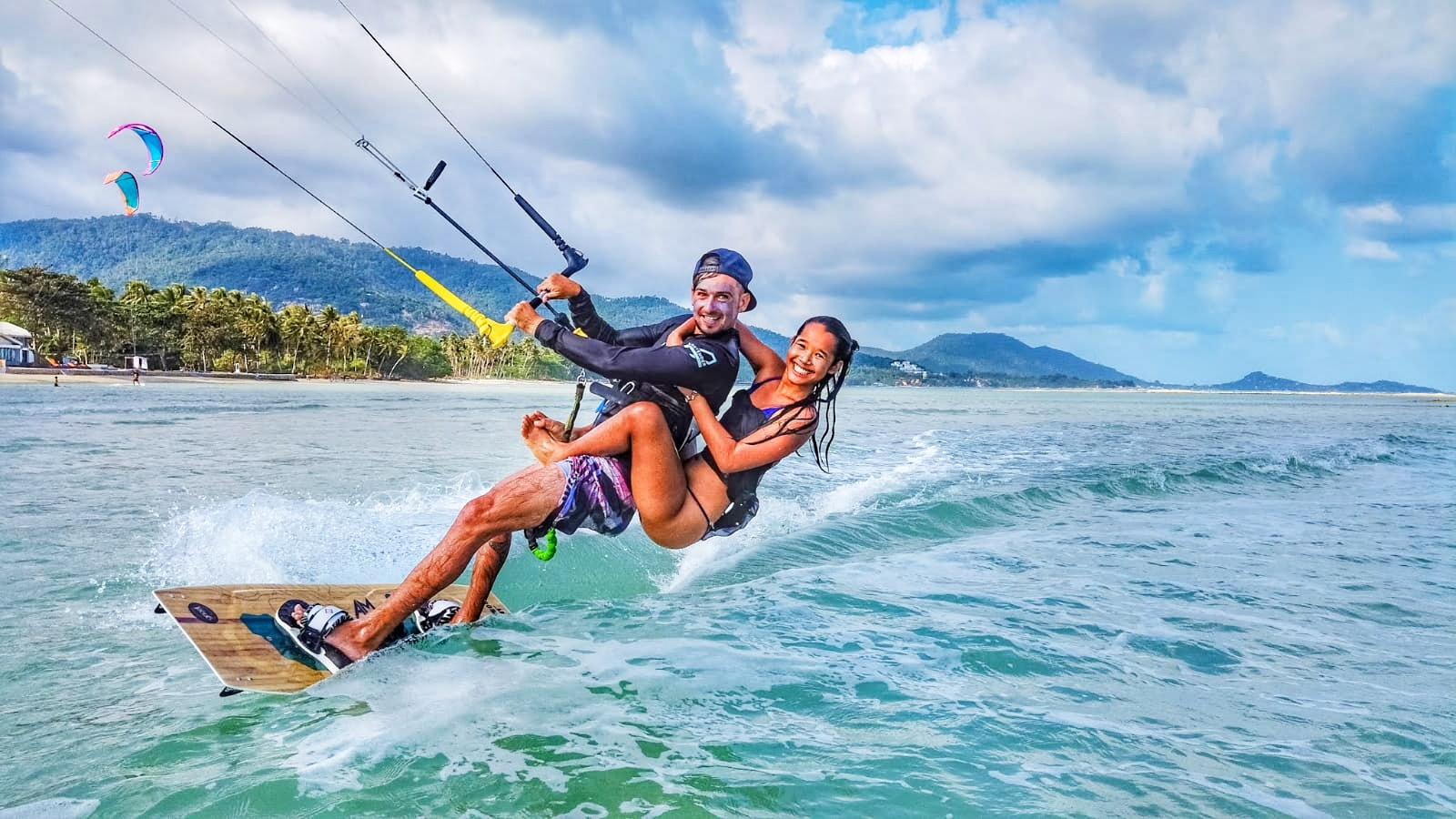 Kitesurfer riding with girl on his back in calm waters.