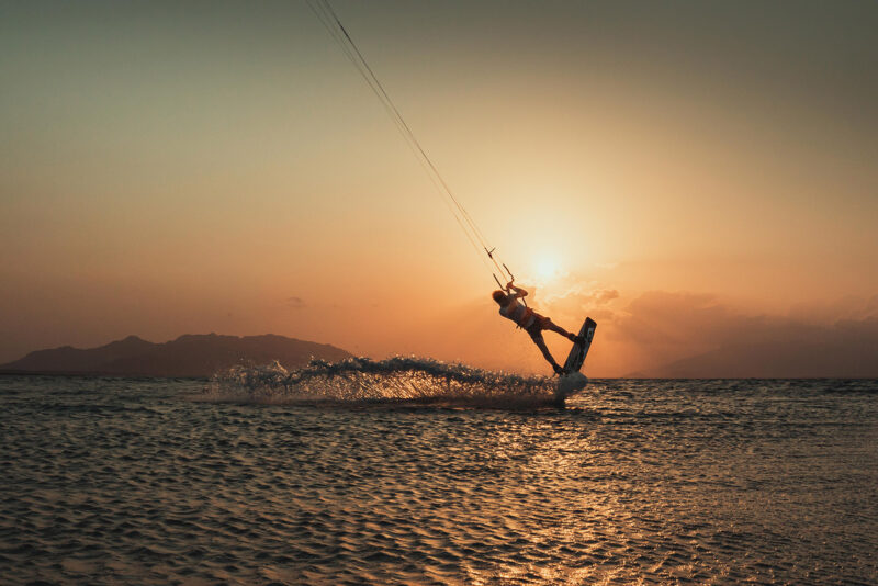 Kitesurfer riding in flat water and sunset.