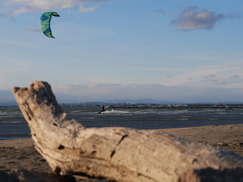 A kitesurfer is cruising in shallow water.