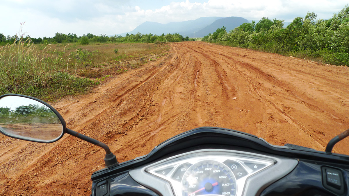 Motor bike and dirt road leading to kampot kitesurf spot in Cambodia