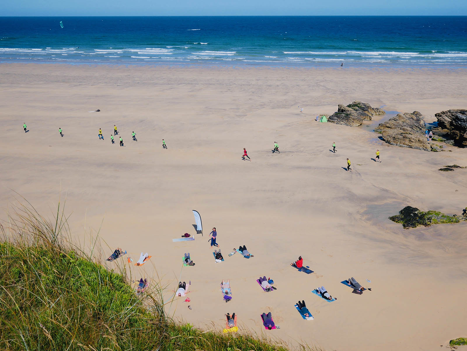 Yoga, surfing and kitesurfing at Gwithian beach.