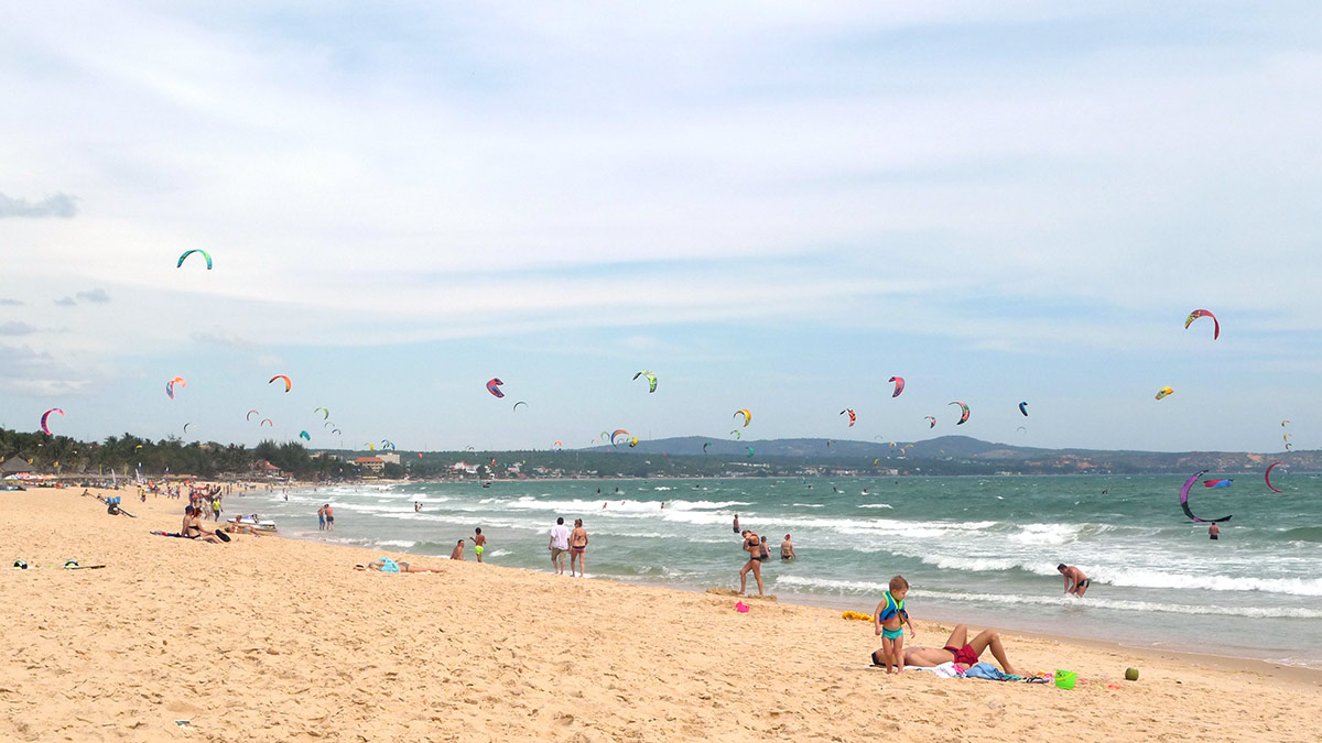 Mui Ne beach with kites flying in the air.