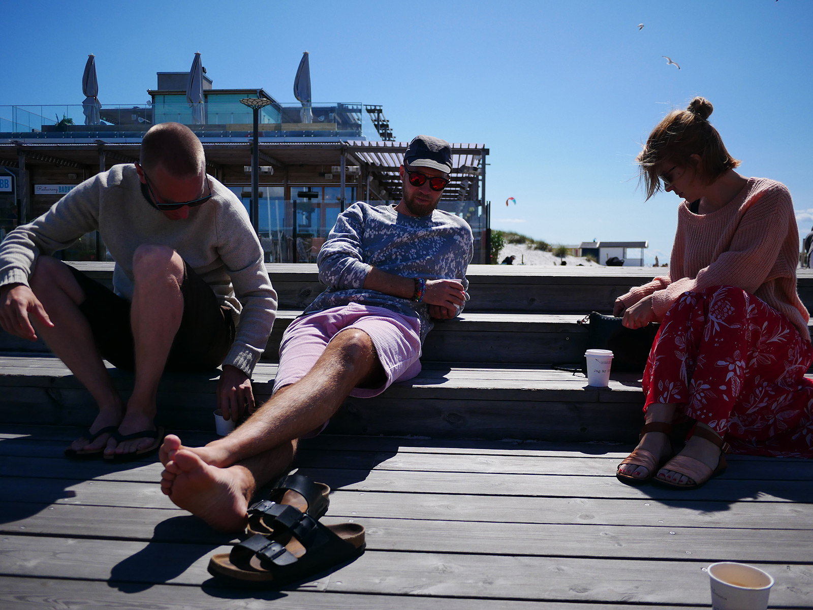 Friends enjoying the sun on a wood deck at Skanor marina.