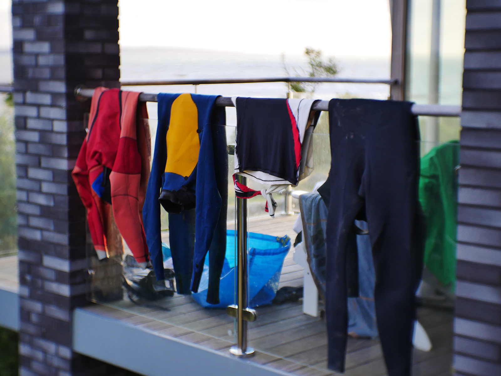 Wetsuits drying on a hand rail.