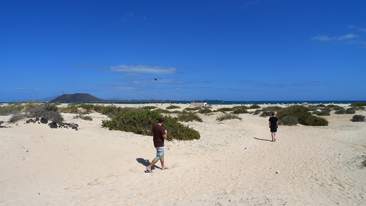 people walking over the dunes to reach Flag Beach kitesurf beach in Fuerteventura