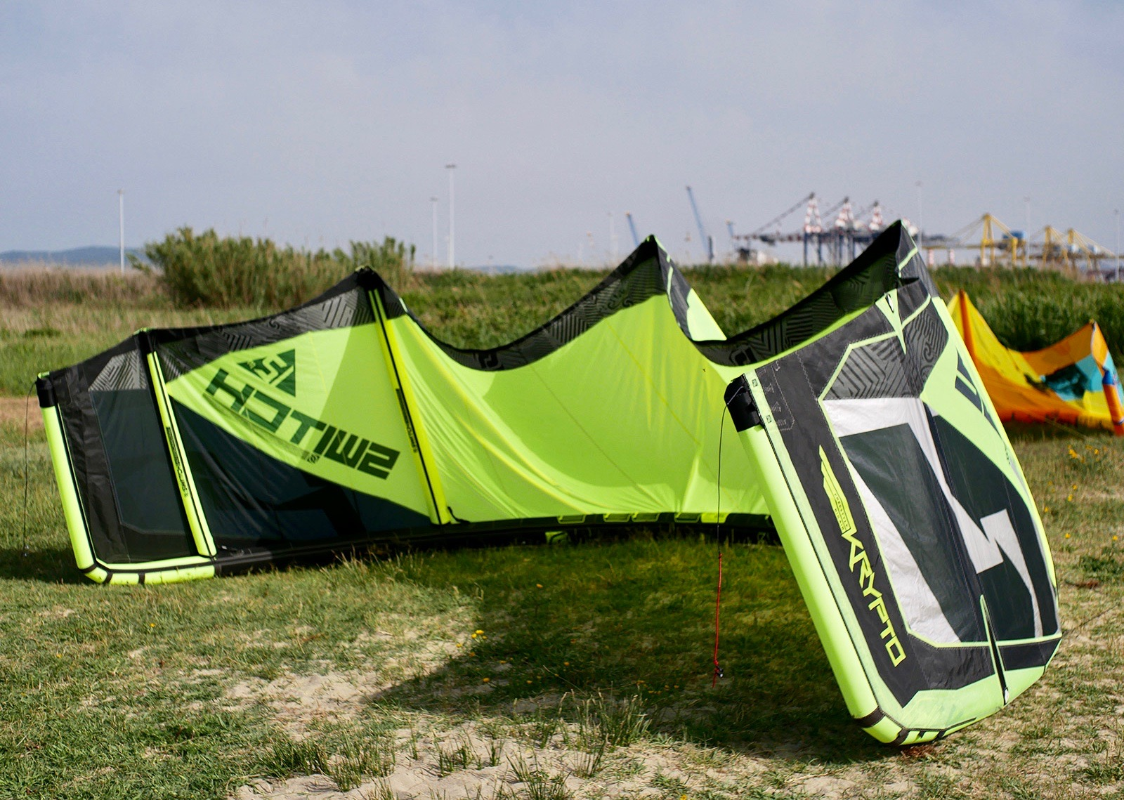 Switch Krypto 12m kite drying on grass with cranes in the background.