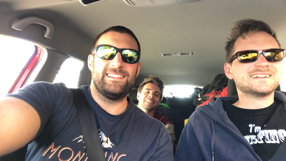 three smiling lads in a car