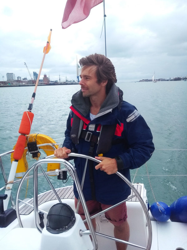 Martin at the helm of a sail yacht